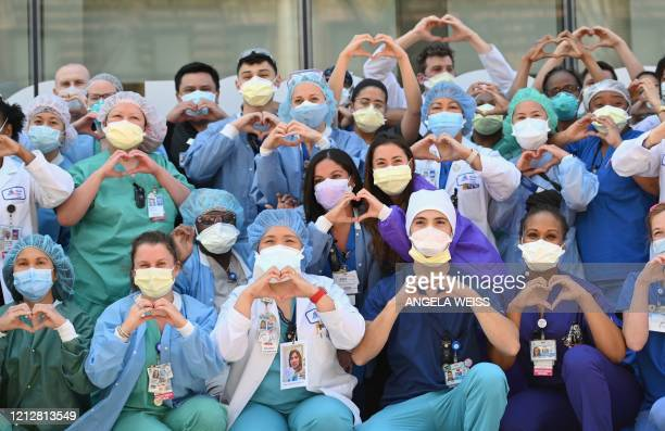 Nurses and healthcare workers gesture hearts in celebration of Nurse Week and International Nurses Day outside Mt Sinai Oueens in the Queens borough...