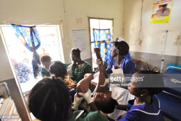 Nurses and midwives carry Mamma Sessay to a stretcher to bring her over to the surgical ward where the only doctor in the district is about one and a...
