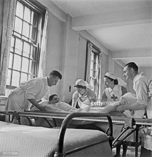 Nurses and orderlies care for a patient in a ward at Shenley Hospital, a military hospital at Shenley near St Albans in Hertfordshire, England during...