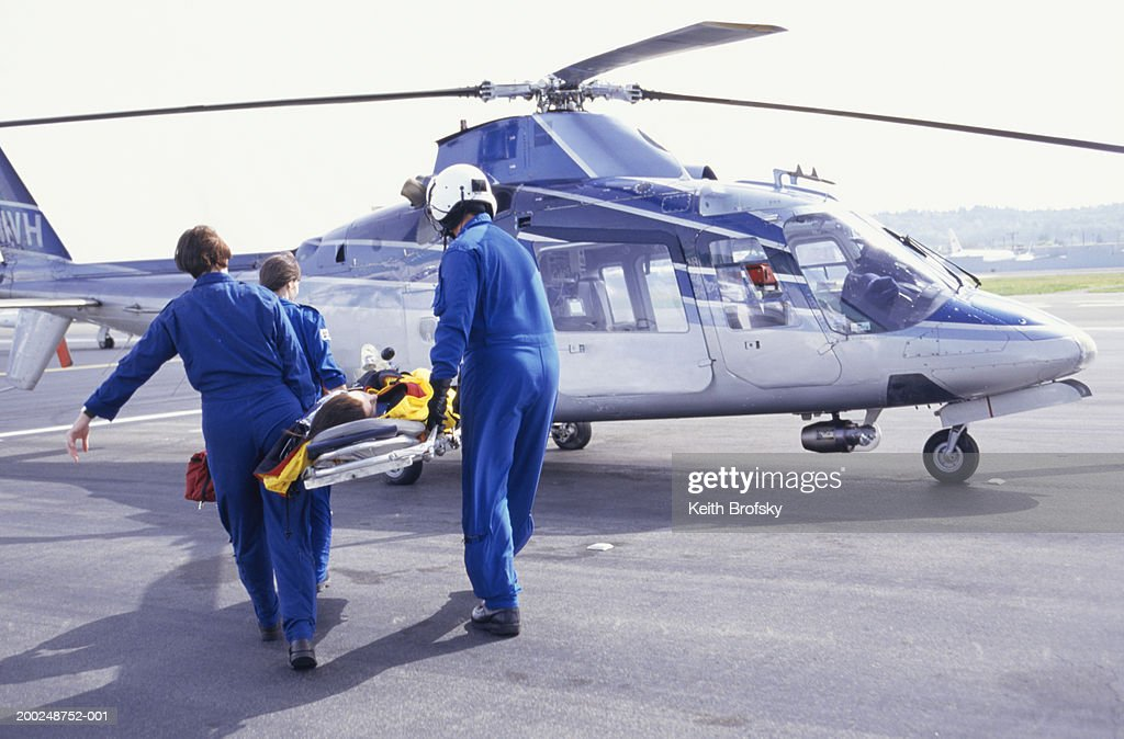 Nurses and pilot carrying patient on stretcher to helicopter : Stock Photo