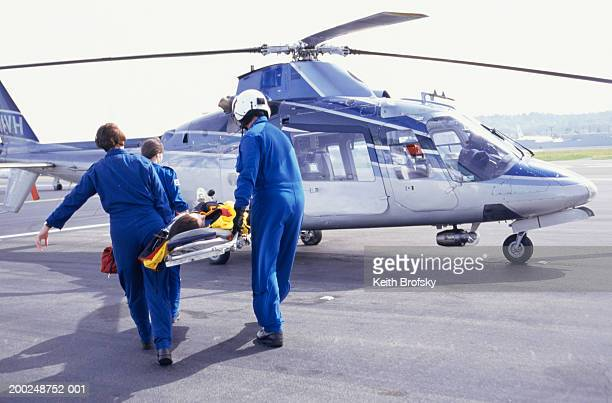 nurses and pilot carrying patient on stretcher to helicopter - medevac stock photos and pictures