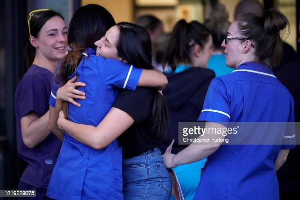Nurses at Aintree University Hospital embrace as they and colleagues applaud the NHS on April 16 2020 in Liverpool United Kingdom Following the...