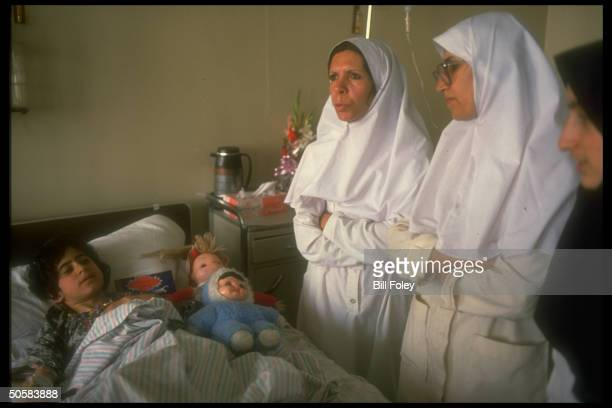Nurses at stuffed animal doll adorned bedside of young earthquake victim at Al Shahati Hospital