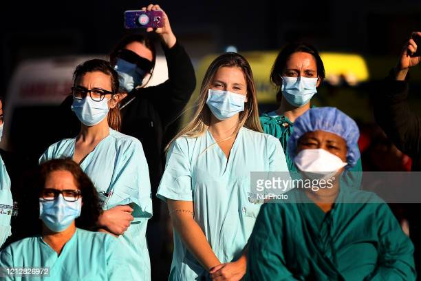 Nurses attend a serenade performed by the Fado music group Serenata ao Luar at Santa Maria Hospital in Lisbon Portugal on May 12 to mark the...
