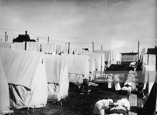 Nurses care for victims of a Spanish influenza epidemic outdoors amidst canvas tents during an outdoor fresh air cure Lawrence Massachusetts 1918