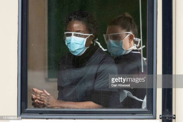 Nurses clean their hands before taking swabs at a Covid-19 Drive-Through testing station for NHS staff on March 30, 2020 in Chessington, United...