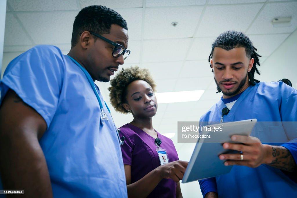 Nurses discussing digital tablet : Stock Photo