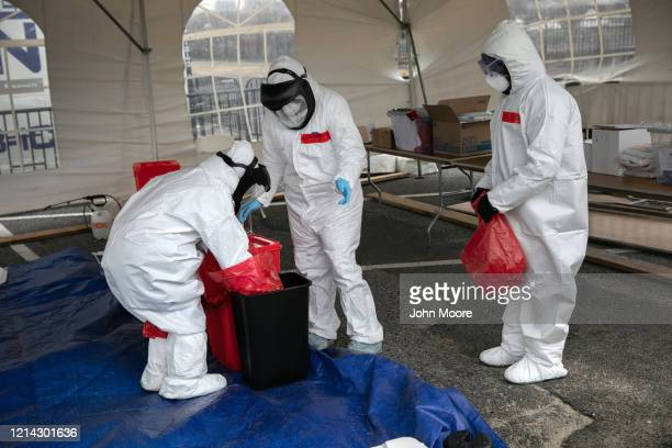 Nurses dressed in personal protective equipment dispose of medical waste at a drive-thru coronavirus testing station at Cummings Park on March 23,...