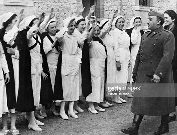 Nurses give the Nationalist salute to General Francisco Franco the leader of Spain's Nationalist forces who defeated the Republican government after...