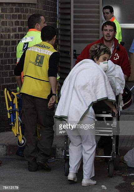 Nurses help evacuate patients from a hospital in Badalona after a fire started in the basement 11 December 2007 AFP PHOTO/JOSEP LAGO