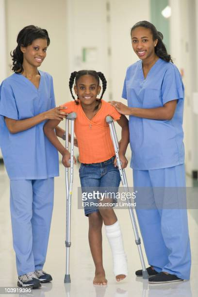 Nurses helping girl with broken leg to use crutches