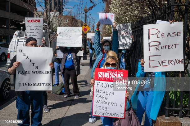 Nurses hold signs during a demonstration for increased personal protection equipment outside Montefiore Hospital in the Bronx borough of New York,...