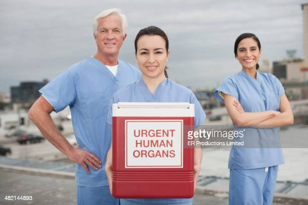 Nurses holding box of urgent human organs on rooftop