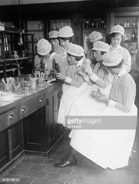 Nurses in white caps of Bellevue Hospital during instruction on bacterialogical lab