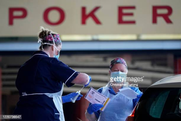 Nurses instruct and help National Health Service workers as they self swab for Coronavirus at a drive through testing site at the Owler Events Centre...