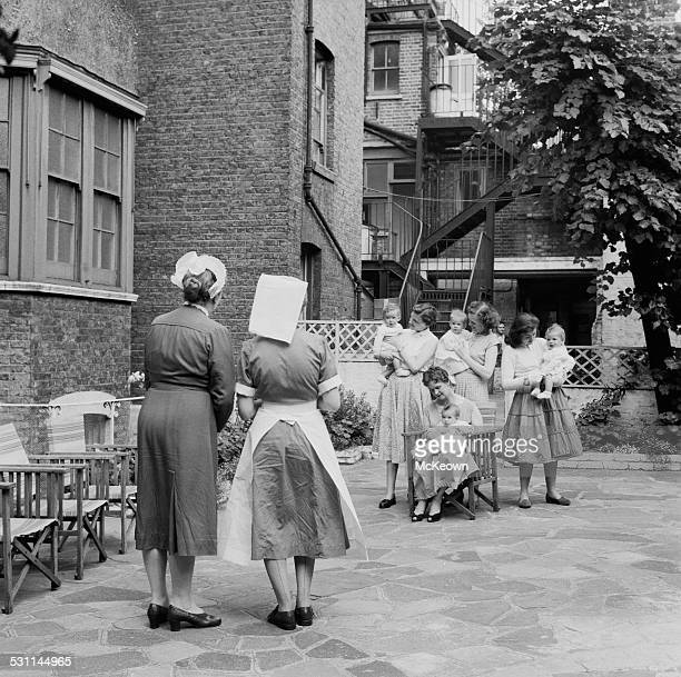 Nurses look on as the Bennett quadruplets are positioned in preparation for a photograph 1958