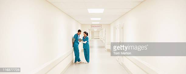 nurses looking at medical chart in hospital corridor - panoramic stock pictures, royalty-free photos & images