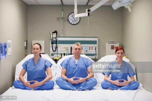 Nurses meditating on hospital beds