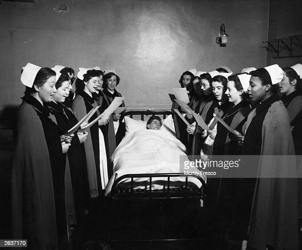 Nurses of Whipps Cross Hospital in London singing Christmas carols to one of the patients in bed