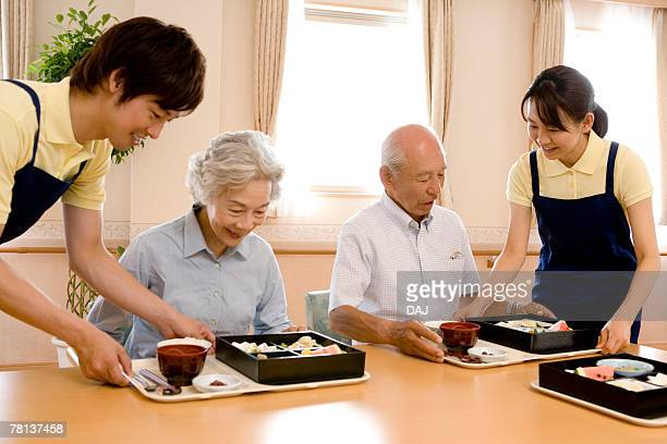 Nurses serving lunch for senior man and woman, smiling