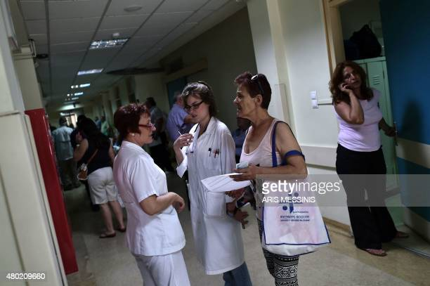 Nurses speak with a patient's relative in an Athens hospital on July 8 2015 With expectations of a Greek exit from the eurozone gathering pace health...
