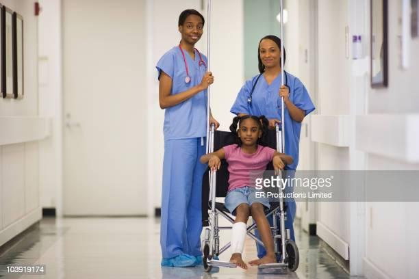 Nurses standing near African American girl in wheelchair