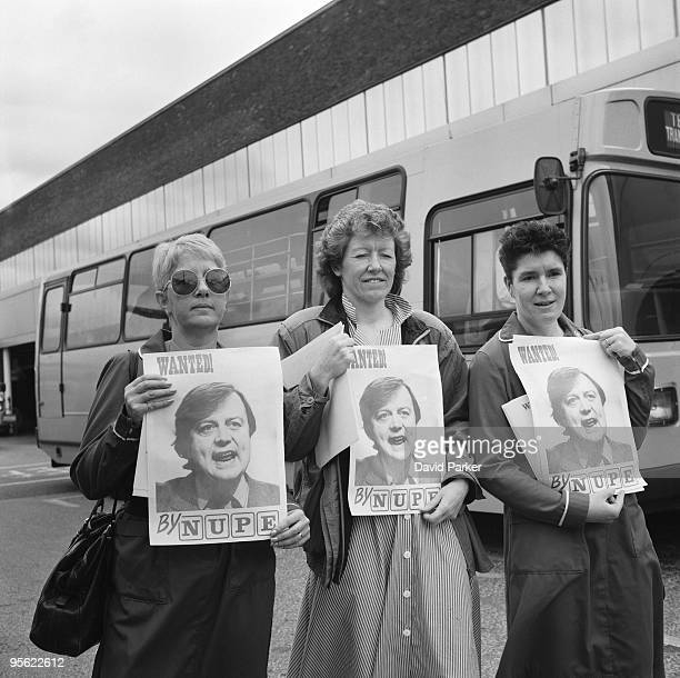 Nurses take part in a NUPE demonstration at Heathrow airport 14th August 1988 They are holding posters with a portrait of Conservative Secretary of...
