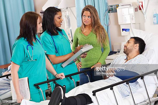 Nurses talking to patient and spouse in hospital recovery room