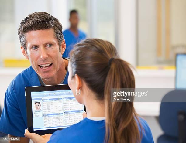 Nurses using digital tablet in hospital