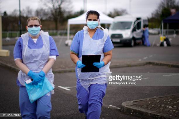 Nurses wait for the next patient at a drive through Coronavirus testing site in a car park on March 12, 2020 in Wolverhampton, England. The National...