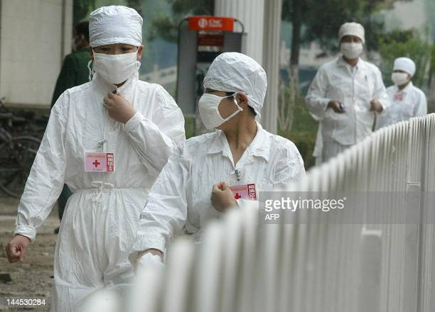 Nurses walk behind a barricade at the quarantined Severe Acute Respiratory Syndrome facility of Xiaotangshan hospital 07 May 2003 on the outskirts of...