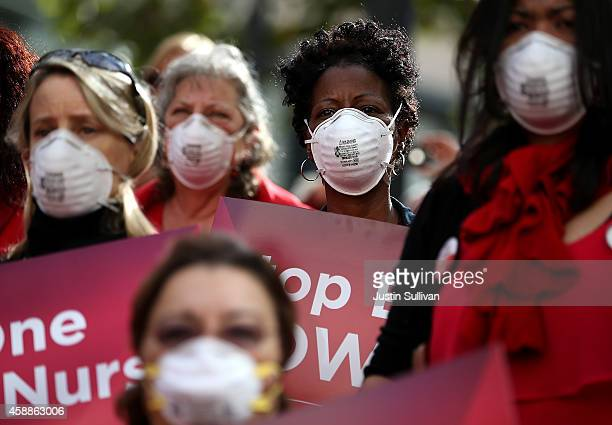 Nurses wear masks and hold signs as they participate in a demonstration outside of the Dellums Federal Building on November 12, 2014 in Oakland,...