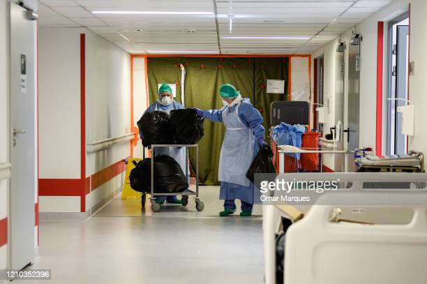 Nurses wear protective suits masks goggles and gloves as they carry bags with contaminated protective equipment inside the Intensive Care Unit for...