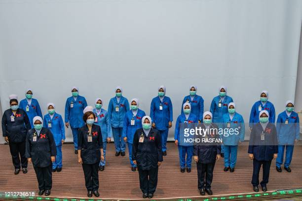 Nurses wearing face masks as a preventive measure against the spread of the COVID19 novel coronavirus pose for a picture during a ceremony to...