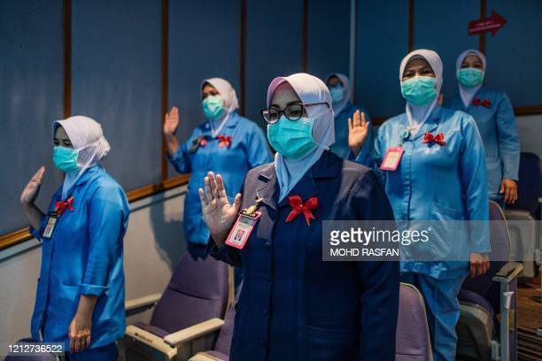 Nurses wearing face masks as a preventive measure against the spread of the COVID19 novel coronavirus read their oath during a ceremony to...