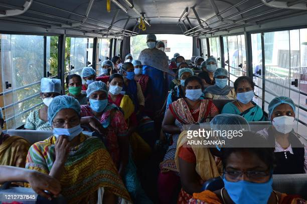 TOPSHOT Nurses wearing facemasks sit in a bus while returning home after a 14 days quarantine as they worked at Rajiv Gandhi hospital in Chennai on...