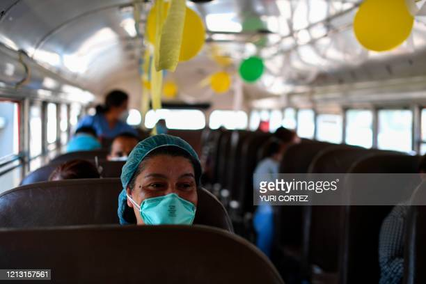 Nurses who work at a hospital on the first line against the coronavirus COVID19 travel on a bus decorated to celebrate International Nurses Day after...