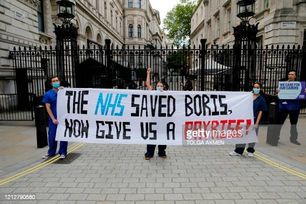 TOPSHOT Nurses who work at central London hospitals protest with placards outside Downing Street in central London on May 13 2020 calling for...