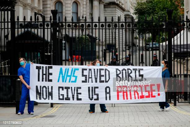 Nurses who work at central London hospitals protest with placards outside Downing Street in central London on May 13, 2020 calling for improved...