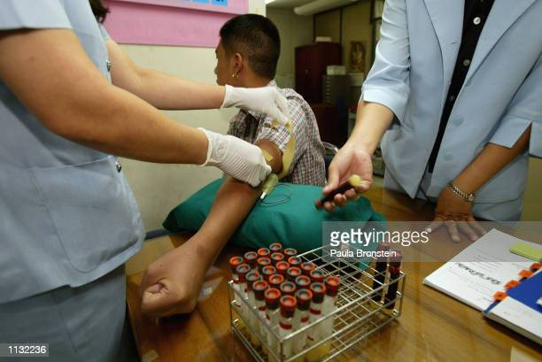 Nurses withdraw blood for testing from a volunteer taking part in the AIDSVAX B/E vaccine trial July 18 2002 at the Boon Mee Clinic in Bangkok...