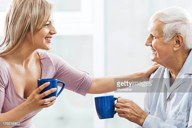 Nursing assistant drinking a cup of coffee with elderly man.