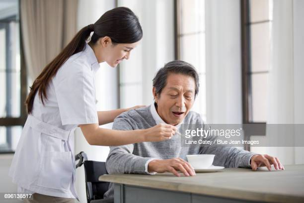 Nursing assistant taking care of senior man in wheel chair