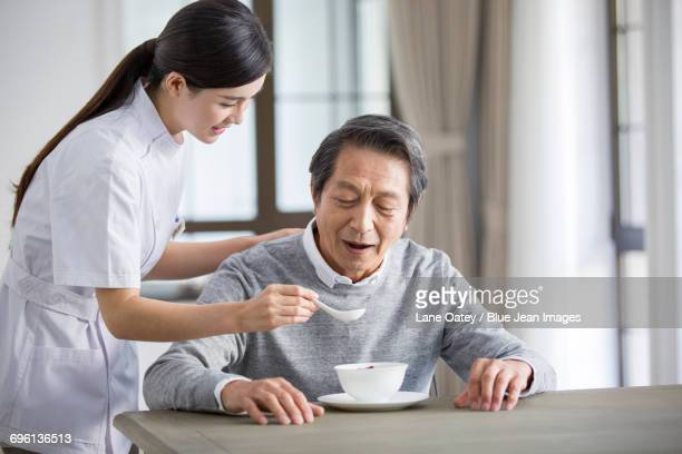 Nursing assistant taking care of senior man