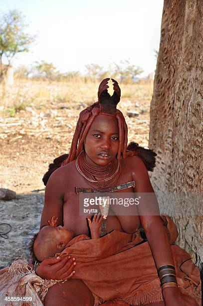 nursing himba mother sitting near hut , opuwo,namibia - opuwo tribe stock photos and pictures