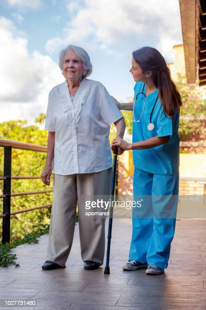 nursing home assistance. helping hand of young hispanic female doctor helping walking exercise senior woman during home visit. - nursing assistant stock pictures, royalty-free photos & images