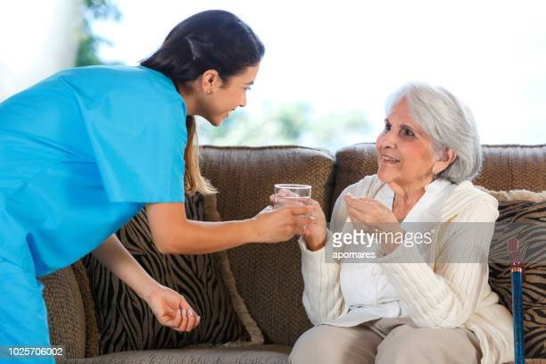 nursing home assistance. young hispanic female doctor helping senior woman taking a pill - taking a pill stock pictures, royalty-free photos & images