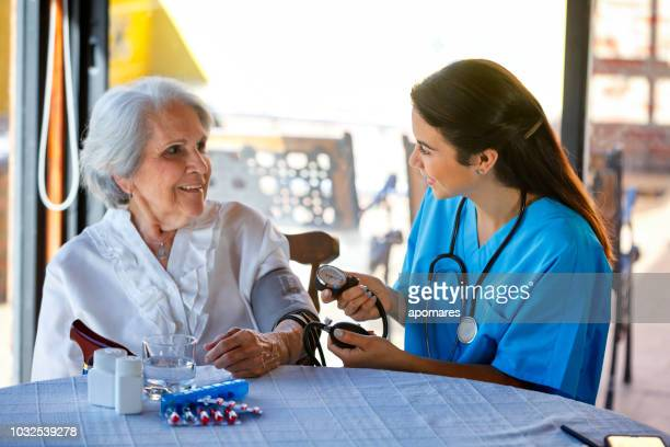 nursing home assistance. young hispanic female doctor taking blood pressure on senior woman - nursing assistant stock photos and pictures
