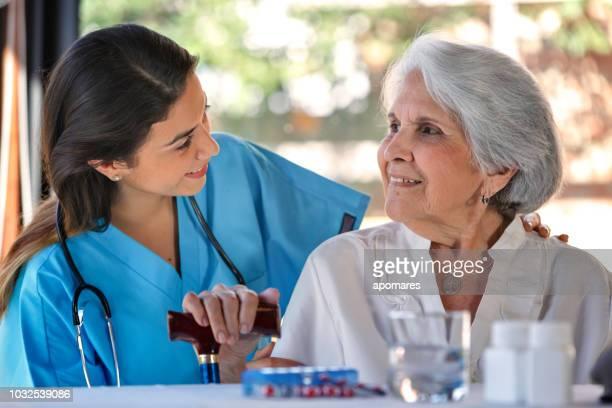 assistance de soins infirmiers à domicile. hispanique de la jeune femme médecin parler à haute femme au cours de la visite à domicile. - aide soignante photos et images de collection
