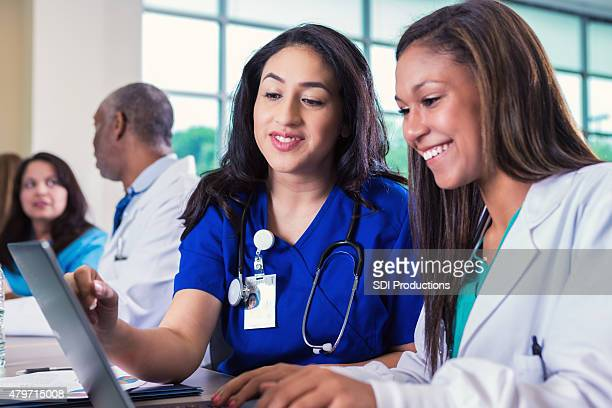 Nursing or medical female professor tutoring college student in class
