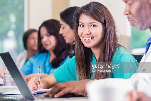 Nursing or medical student smiling while taking notes in class